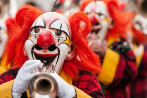 Colorful clown group playing the trumpet at Basel fasnacht festival.